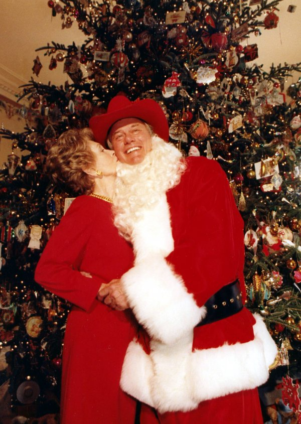 Nancy Reagan plants a kiss on the cheek of Santa Claus, better known as Larry Hagman.