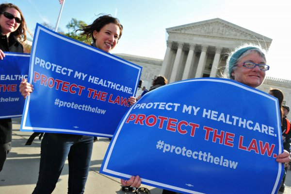 Protesters gather in front of the U.S. Supreme Court for the healthcare case in Washington