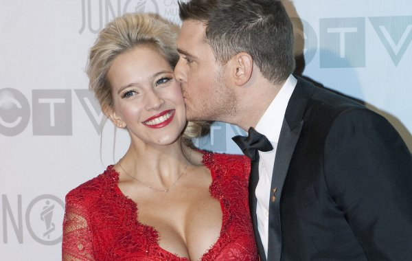 Singer Michael Buble kisses his pregnant wife Luisana