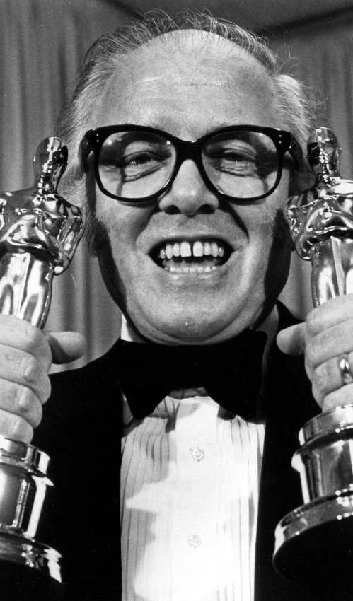 "Richard Attenborough holds up two Oscars for the movie, ""Gandhi."""