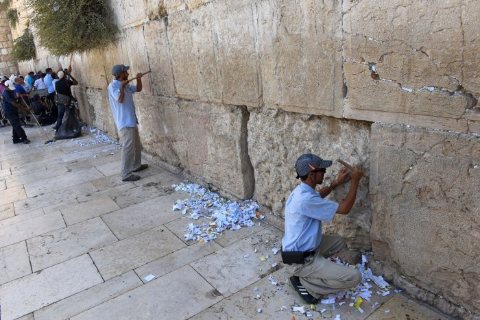 in pictures workers clear prayer notes from western wall before