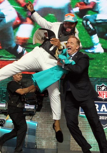 Christian Wilkins jumps into the arms of NFL Commissioner Roger Goodell