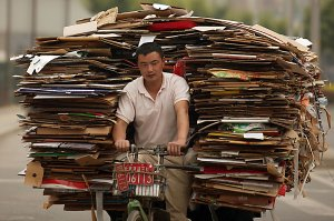 Hombre ciclos depósito de basura a la basura en Pekín