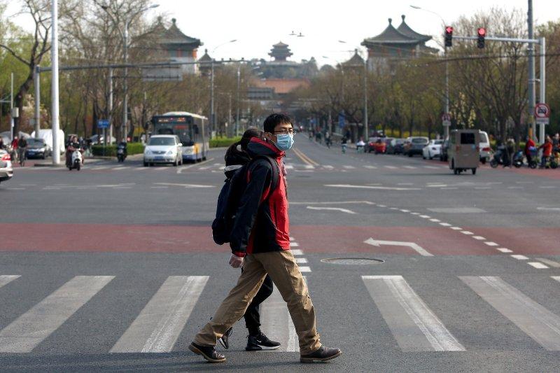 Personas en China con máscaras protectoras caminan el jueves por una intersección en el centro de Beijing. Foto de Stephen Shaver / UPI