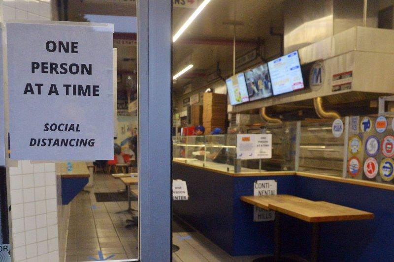 Una pizzería en Los Ángeles aplica una política de distanciamiento social con un cartel en su entrada, visto el lunes. Las pérdidas laborales creadas por el brote de coronavirus han dado como resultado millones de nuevas solicitudes de beneficios por desempleo. Foto de Jim Ruymen / UPI