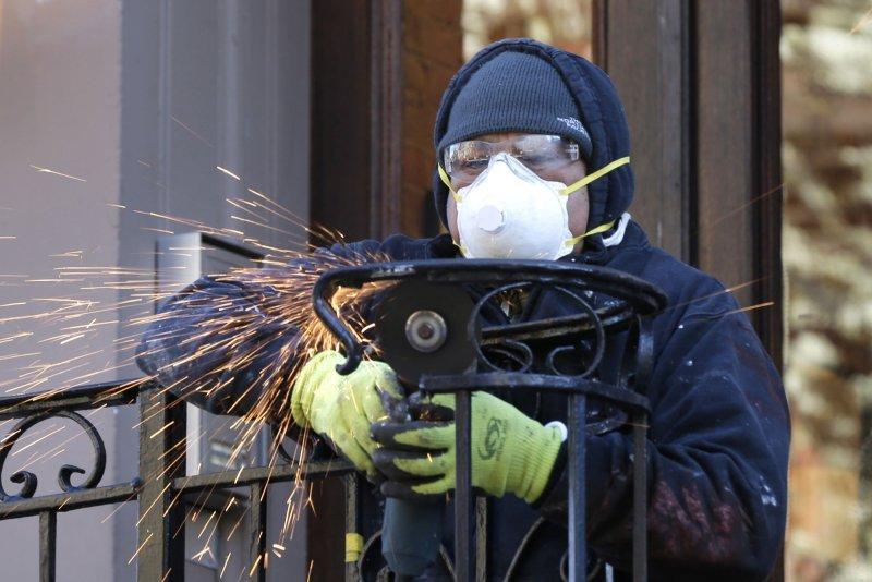 Un trabajador repara una barandilla con una máscara protectora y guantes en la ciudad de Nueva York el martes. Foto de John Angelillo / UPI
