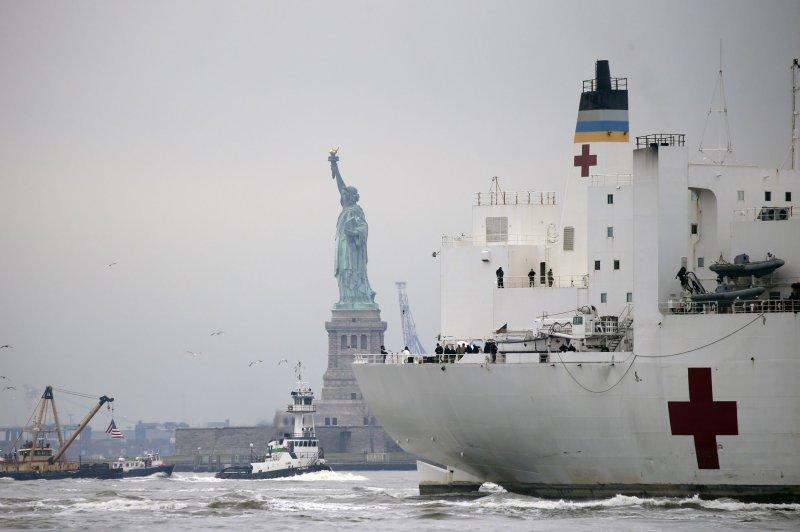 El buque USNS Comfort Navy pasa el lunes por la Estatua de la Libertad en ruta hacia el río Hudson en la ciudad de Nueva York para servir como hospital flotante. Foto de John Angelillo / UPI