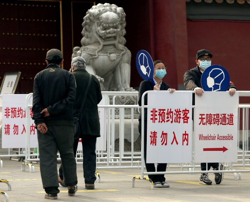 Los voluntarios chinos se aseguran de que los visitantes de un parque usen máscaras faciales en medio de informes de una disminución en la amenaza de COVID-19 en Beijing el martes. Foto de Stephen Shaver / UPI