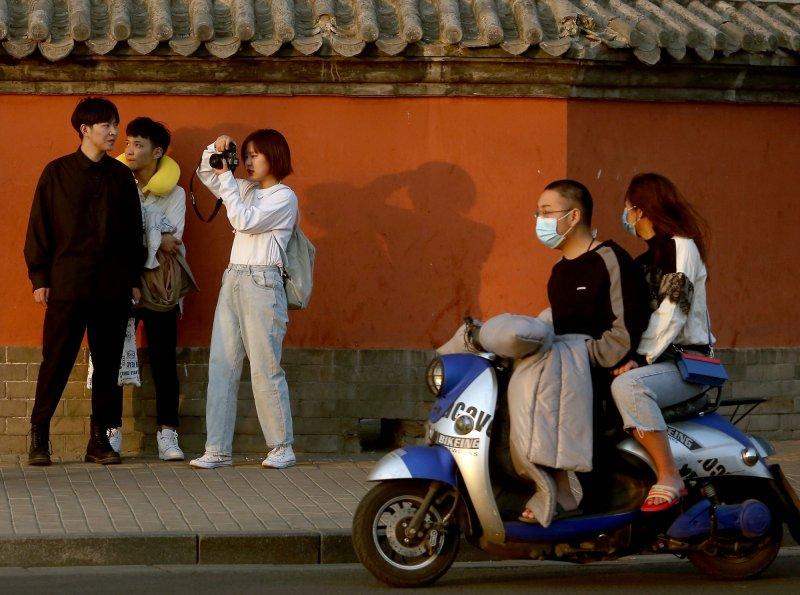 Un grupo de estudiantes de cine chinos, que no usan máscaras faciales, visitan un área turística cuando la amenaza del mortal coronavirus se desvanece en Beijing el domingo. Foto de Stephen Shaver / UPI