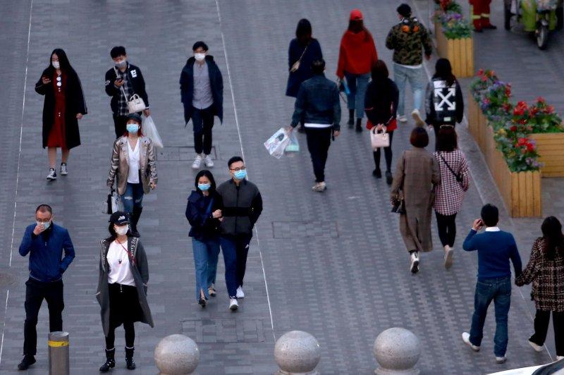 Las personas usan máscaras faciales protectoras para protegerse contra la propagación de la enfermedad por coronavirus el martes mientras visitan un área comercial en Beijing, China. Foto de Stephen Shaver / UPI