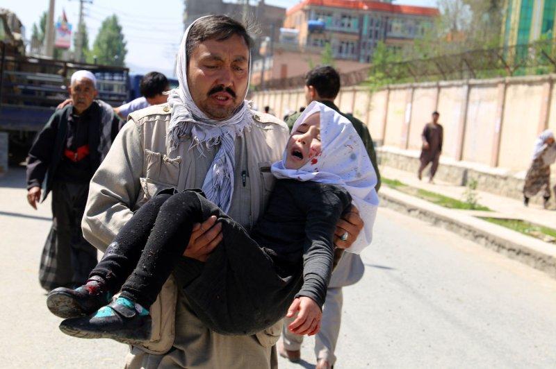 Un hombre lleva a un niño herido tras un atentado suicida en Kabul, Afganistán. La Misión de Asistencia de la ONU instó a poner fin a los ataques civiles, particularmente a la luz del brote de coronavirus. Foto de archivo por Ezatullah Alidost / UPI