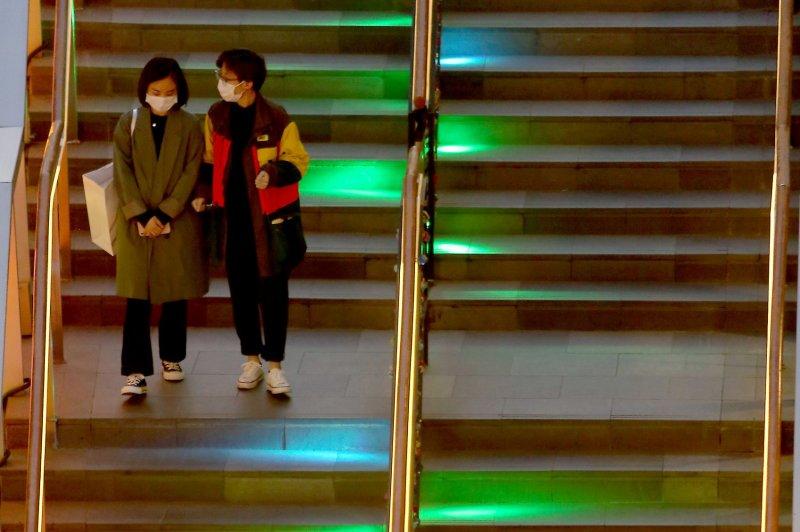Residentes usan máscaras faciales protectoras mientras visitan un área de compras en Beijing, China, el martes. Foto de Stephen Shaver / UPI