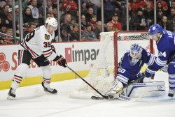 Blackhawks Hayes shoots as Maple Leafs Gustavsson and Liles defend in Chicago