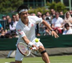 Kei Nishikori returns the ball at 2013 Wimbledon Championships