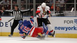 New York Rangers Sean Avery gets knocked to the ice by Ottawa Senators Aton Volchenkov at Madison Square Garden