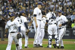 Members of the Milwaukee Brewers meet on the mound with pitcher Kameron Loe during game 6 of NLCS in Milwaukee, Wisconsin