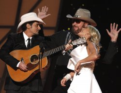 Hosts Brad Paisley and Carrie Underwood joke with Hank Williams Jr. at the 2011 CMA Awards in Nashville
