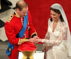 Prince William places the ring on the hand of Kate Middleton in London