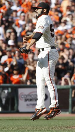 Giants Sergio Romo leaps in the air after striking out San Diego Padres Yorvit Torrealba in San Francisco