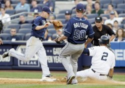 New York Yankees Derek Jeter slides into first base as Tampa Bay Rays Reid Brignac tags the base at Yankees Stadium in New York