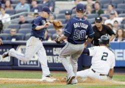 New York Yankees Derek Jeter slides into first base as Tampa Bay Rays Reid Brignac tags the base at Yankees Stadium in New York