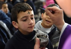 A Priest Makes A Cross On A Boy's Forehead On Ash Wednesday In West Bank
