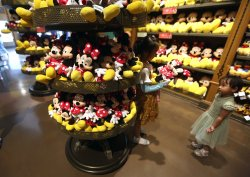 Chinese girls inspect Mickey and Minnie Mouse dolls in Shanghai Disney, China