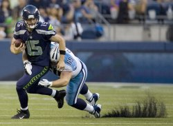 Seattle Seahawks quarterback Matt Flynn scrambles against Tennessee Titans defensive tackle Zach Clayton in Seattle.