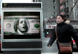 Woman walks past billboard of USD100 in Beijing