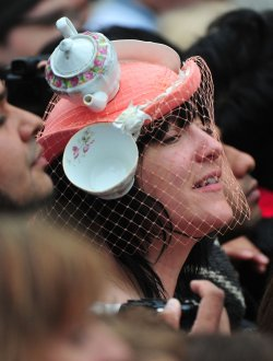 A woman with a tea pot inspired hat watches outside Westminster Abbey in London