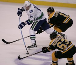Canucks Burrows chased by Bruins Marchand and Campbell in game 6 of the NHL Stanley Cup Finals in Boston, MA.