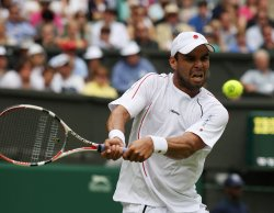 Alejandro Falla plays a backhand on the first day of Wimbledon.