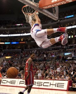 Los Angeles Clippers Blake Griffin swings from the rim after dunk over Milwaukee Bucks Brandon Jennings in Los Angeles