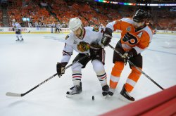 Blackhawks Brent Seabrook and Flyers Simon Gagne fight for the puck during the 2010 Stanley Cup Final