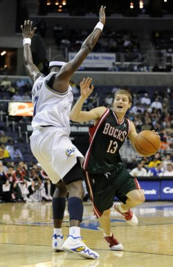 Bucks Ridnour drives past Wizards Blatche in Washington