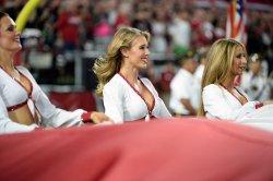 Cardinals' cheerleader helps wave flag