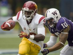 USC Trojans wide receiver Robert Woods is tackled by Washington Huskies linebacker John Timu after catching a pass in Seattle.
