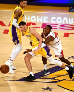Lakers guard Lonzo Ball drives by Bulls guard Kris Dunn
