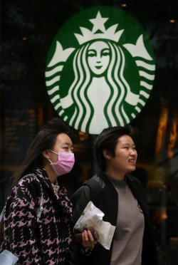 Chinese walk past a Starbucks in central Beijing