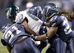 Philadelphia Eagles tight end Brent Celek, center, is tackled by Seattle defenders Kan Chancellor, left, Atari Bigby, right, and Earl Thomas, back, after catching a pass for a first down in Seattle.