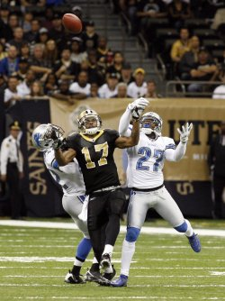 New Orleans Saints receiver Robert Meachem has the ball tipped into the air by Detroit Lions defenders at the Mercedes-Benz Superdome