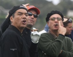 Actors George Lopez and Andy Garcia smoke cigars during the Pebble Beach 3M Celebrity Challenge