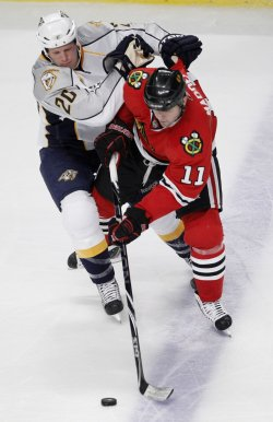 Blackhawks MAdden and Predators Suter go for puck in Chicago