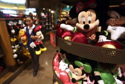 A Chinese saleswoman stocks Disney dolls in Shanghai Disney, China