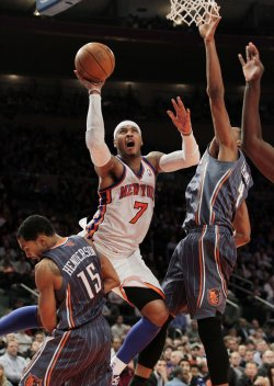 New York Knicks Carmelo Anthony shoots between Charlotte Bobcats Gerald Henderson and Derrick Brown at Madison Square Garden in New York
