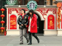 A Chinese couple walks past a Starbucks store adorned with traditional Chinese decorations in Beijing