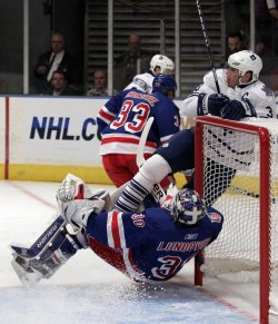 Toronto Maple Leafs Dion Phaneuf slams into New York Rangers Henrik Lundqvist at Madison Square Garden in New York