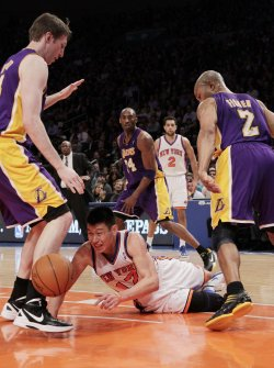 Los Angeles Lakers Kobe Bryant and Derek Fisher watch New York Knicks Jeremy Lin dive for a loose ball at Madison Square Garden in New York