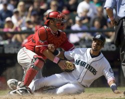 Seattle Mariners' Franklin Gutierrez (R) is tagged out by Los Angeles Angels catcher Mike Napoli i.