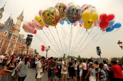 A Chinese Disney employee sells Disney balloons in Shanghai Disneyland Resort, China